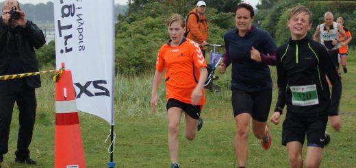 3 løbere på målstregen med fotograf i baggrunden til NyborgTri 4-18-4