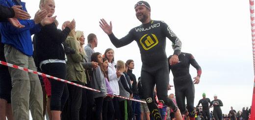 Løbere i våddragt på stranden hilser på tilskuerne