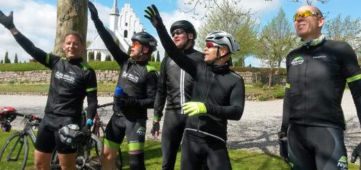 Cykkelryttere nyder søndagssolen med Ullerslev Kirke i baggrunden.